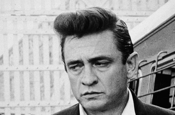 American country singer and songwriter Johnny Cash (1932 - 2003) walks inside the gates of Folsom Prison, preparing to perform his fourth concert for inmates there, California, 1964. (Photo by Hulton Archive/Getty Images)